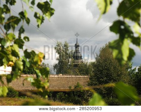 View Of The Dome Of An Old Wooden Church In The Middle Of Rural Landscapes, In The Middle Of The Vil
