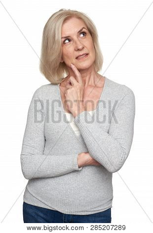 Portrait Of Senior Woman Looking Up And Thinking