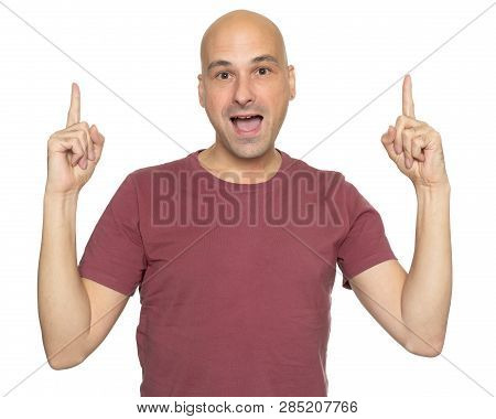 Cheerful Bald Guy Pointing His Fingers Up. Isolated