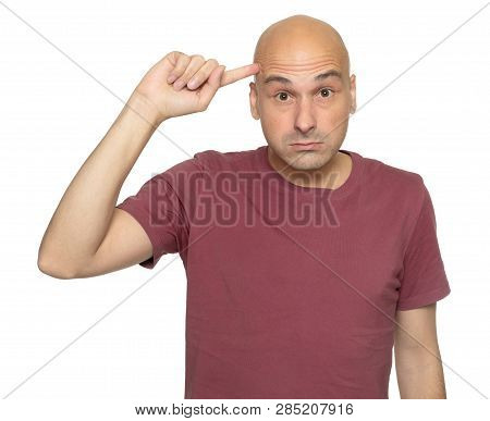 Bald Man Holds His Finger At The Temple Isolated