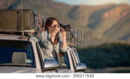 Young Asian Woman Traveler And Photographer Sitting On The Car Window Taking Photo On Road Trip In N