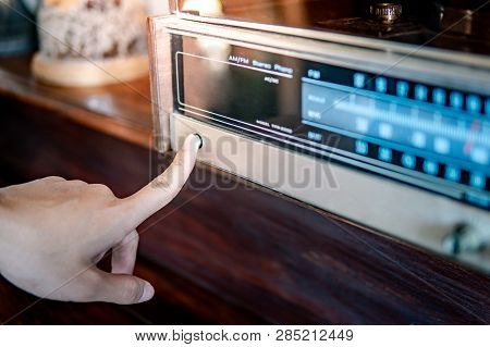 Male Hand Turning On Retro Radio By Pressing Power Button. Listen To Music Or News With Old Classic