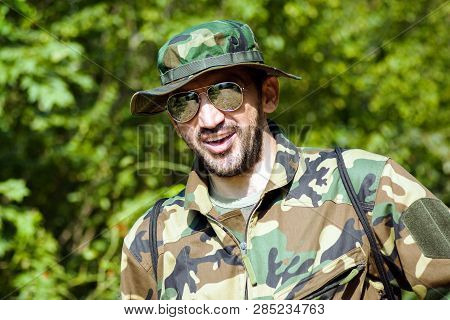 Portrait Of Smiling Man In Military Uniform In Nature On Green Background, Adventure In Wilderness.