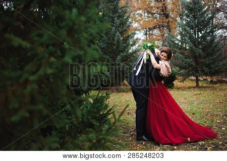 Romantic Embrace Of Newlyweds. Couple Walks In The Park.