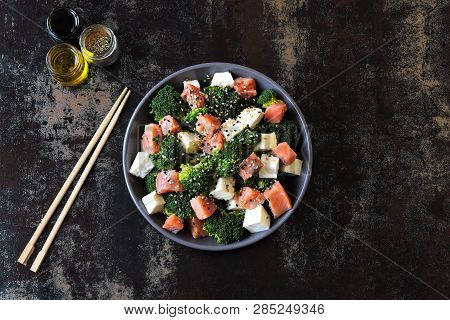 Poke bowl with salmon. Salmon broccoli sesame poke. Top view. Food sticks. poster