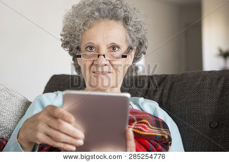 Smiling Elderly Woman In Glasses Reading Internet News On Table. Attractive Senior Lady Looking At C