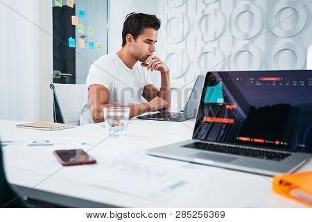 Young Coworkers People Working At Work Place Office While Sitting At Table And Analyzing Trends On M
