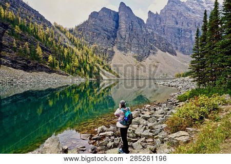 Hiker In Front Of Reflective Lake Agnes