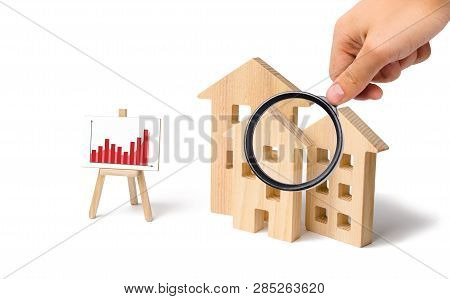Magnifying Glass Is Looking At The Wooden Houses With A Stand Of Graphics And Information. Growing D