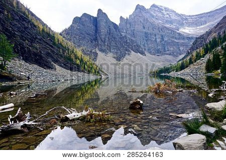 Mountain Reflections In Calm Water Of Lake Agnes