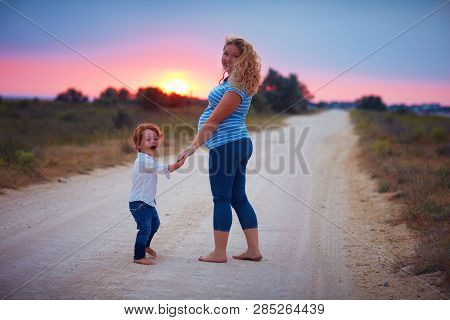 Happy Pregnant Mother And Toddler Baby Boy Walking Barefoot On Countryside Road At Summer Sunset