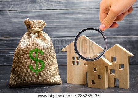 Magnifying Glass Is Looking At The Three Houses Near A Bag With Money. Real Estate Acquisition And I