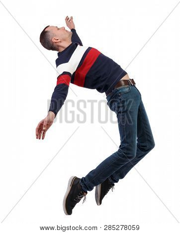 Side view of man in zero gravity or a fall. guy is flying, falling or floating in the air.   side view of person.  Isolated over white background. Stylish guy in a sweater in zero gravity.