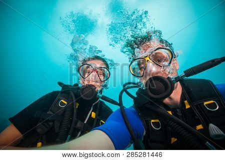 Young woman and man scuba divers making selfie. Underwater sport and leasure activities.