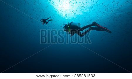 Young woman and man scuba divers exploring. Underwater sport and leasure activities.