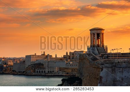 View of Siege Bell War Memorial as old walls and fortress on background under beautiful evening sky in Valletta, Malta.