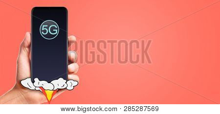 male hand hold launching 5G smartphone, on living coral background.