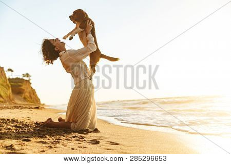 Image of gorgeous woman 20s hugging her dog while sitting on sand by seaside