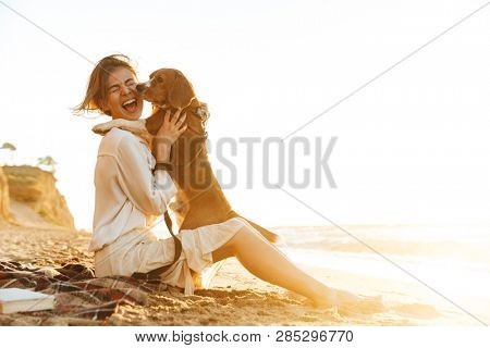 Image of cheerful woman 20s hugging her dog while sitting on sand by seaside