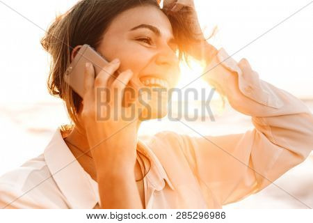 Image of european woman 20s smiling and talking on cell phone while walking by seaside