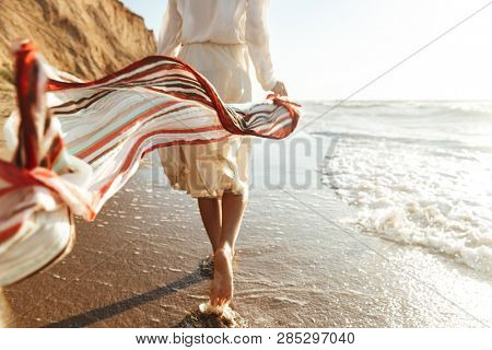Portrait of positive girl 20s walking with waving scarf along seashore