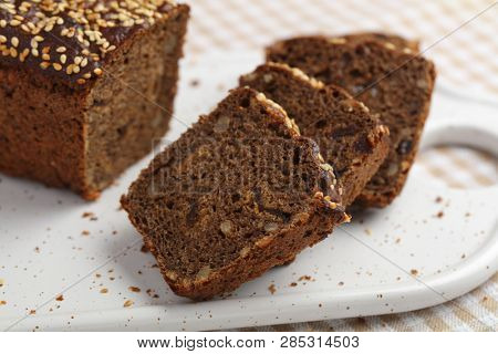 Rye bread with grains and raisins on a cutting board