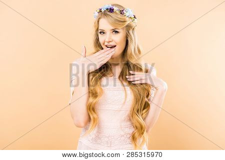 smiling woman in pink lacy dress and floral wreath holding hand near mouth and looking at camera on yellow background poster