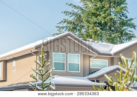A perfect neighbourhood. Houses in suburb at Winter in the north America. Fragment of a luxury house covered nice snow.