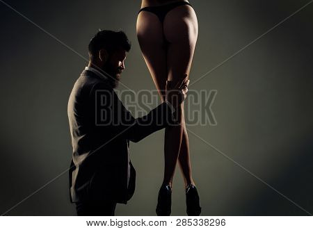 Rich man is sexy wonam. Sexy ass, bum, butt. Female ass in underwear. Sexy couple, sensual couple. Long pretty woman legs. Handsome bearded in suit. Woman dominates the man, sex games, obeys man poster