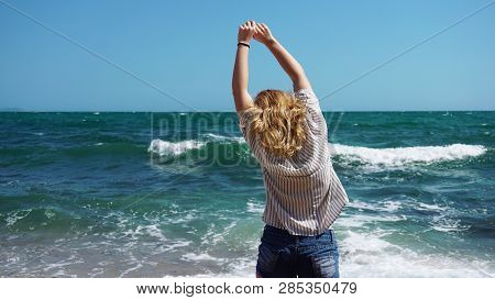 Beautiful Bohemian Styled And Tanned Girl At The Beach Against The Backdrop Of Sea Waves
