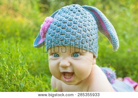 Easter Holidays! Cute Baby In A Easter Bunny Of Lamb Costume In The Green Spring Grass. Smiling Baby