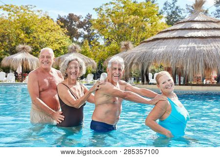 Senior group has fun with aqua fitness in the swimming pool of the hotel
