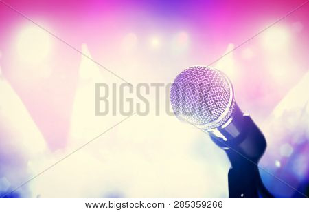 Microphone and bright colorful stage lights. Concert, music show, gig. Singing performance.