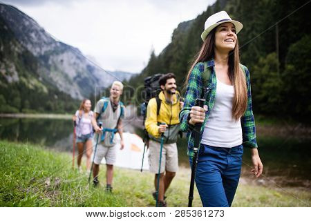 Group Of Smiling Friends Hiking With Backpacks Outdoors. Travel, Tourism, Hike And People Concept.