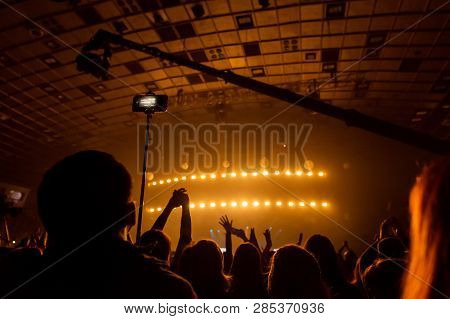 Silhouettes of crowds of spectators at a concert with smartphones in their hands. poster