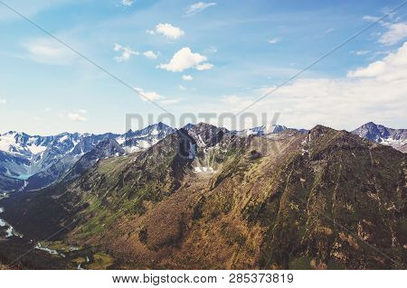 The Top Of The Mountain With The Snow On The Slopes On The Background Of Blue Sky With White Clouds.