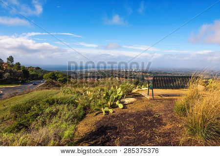 Huntington Beach and Newport Beach viewed from the Vista Ridge Park in California with a bench in the foreground. poster
