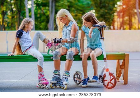 Pretty little girls sitting on the green branch in the skatepark and putting on rollerskates