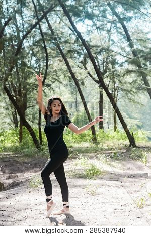 Theb Eauty Lady Wearing Black Suit And Satin Ballet Shoes,posing Ballet Pattern,in Forest,blurry Lig