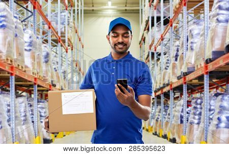 mail service, technology and shipment concept - happy indian delivery man or warehouse worker with smartphone and parcel box in blue uniform over goods background