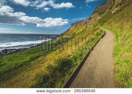 Close-up hiking path next to the Northern Ireland shoreline. Picturesque landscape. Steep green slope. Grass covered Irish hill next to the ocean. Ideal place for the tourist outdoor activity.