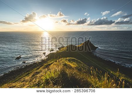 Panoramic view from Northern Ireland shoreline to the sunset ocean. Amazing landscape. The grass covered land next to the sunlit ocean water. Beauty of the wild Irish nature under the sun lights.