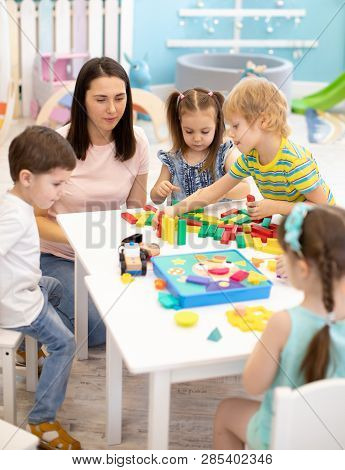 Little Children Playing Different Toys With Teacher In Daycare. Kids Building Color Blocks. Educatio