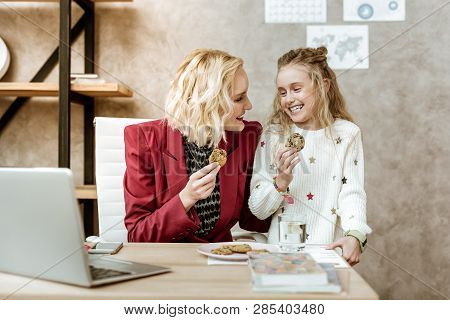 Joyful And Laughing Daughter With Her Mother Eating Tasty Chocolate Cookies