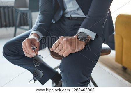 Close-up Fashion Image Of A Businessman Who Is Sitting On The Chair And Holding Sunglasses