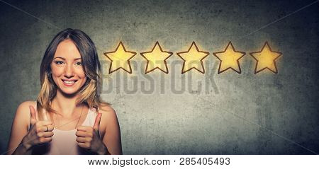 Сheerful Beautiful Woman Smiling Showing Thumb Up Like Gesture Choosing Five Stars Rating. Excellent
