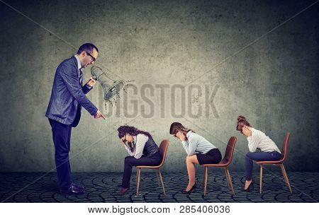 Authoritarian Angry Boss Businessman Screaming In Megaphone Giving Orders To Sad Looking Down Female