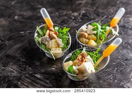 Modern European Appetizer. Mini Salad With Gorgonzola, Pear And Roasted Cashews. Orange Dressing In