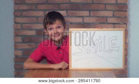 Little Boy Showing Whiteboard With Handwriting Word Smile. Schoolboy With Happy Smiling On His Face.