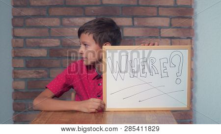 Child Sitting At The Desk Holding Flipchart With Lettering Where On The Background Red Brick Wall. S